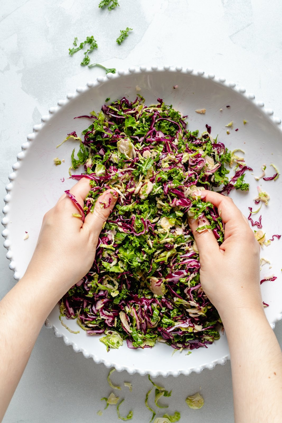 massaging dressing into a brussels sprouts kale apple salad