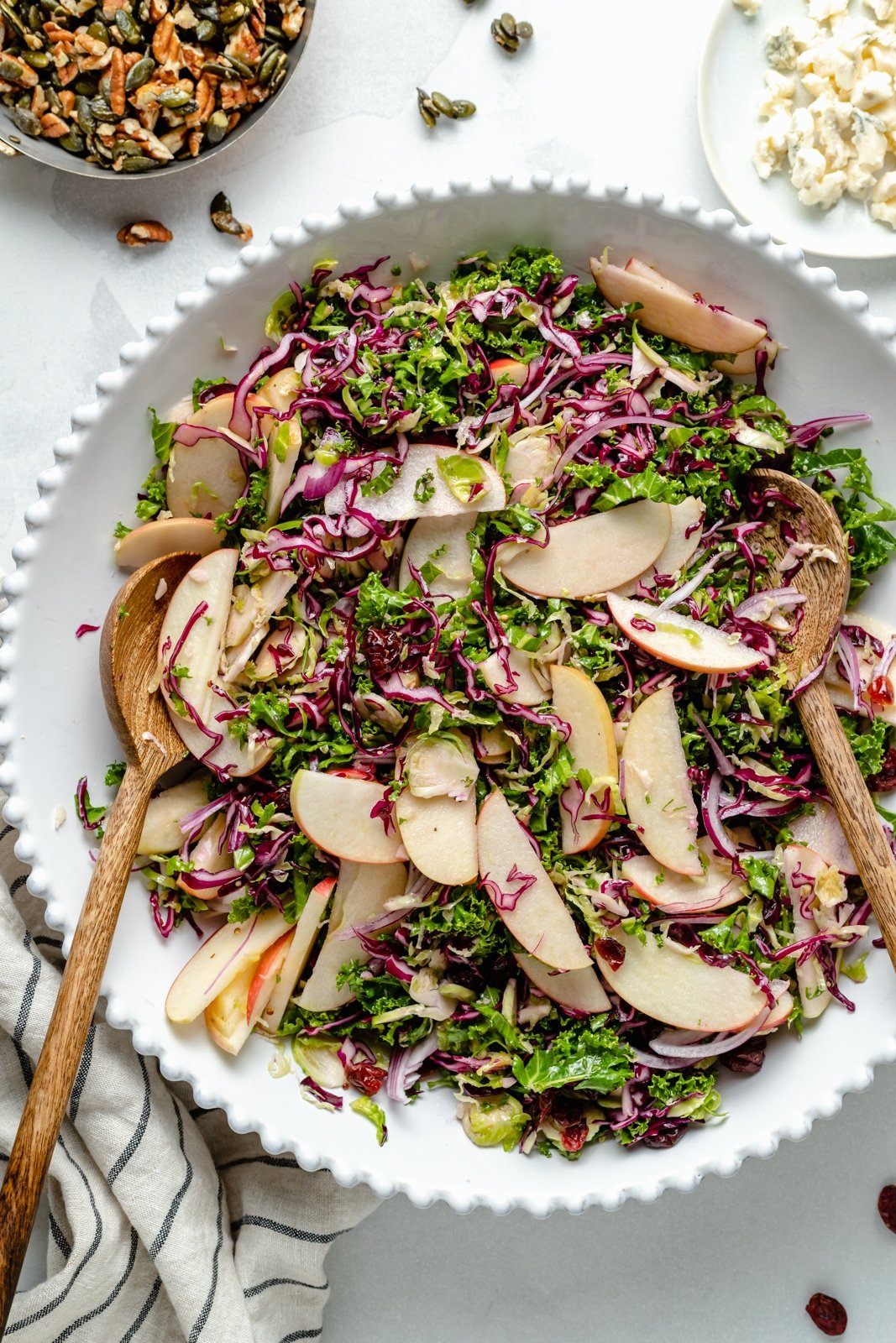 kale apple salad in a bowl with serving spoons