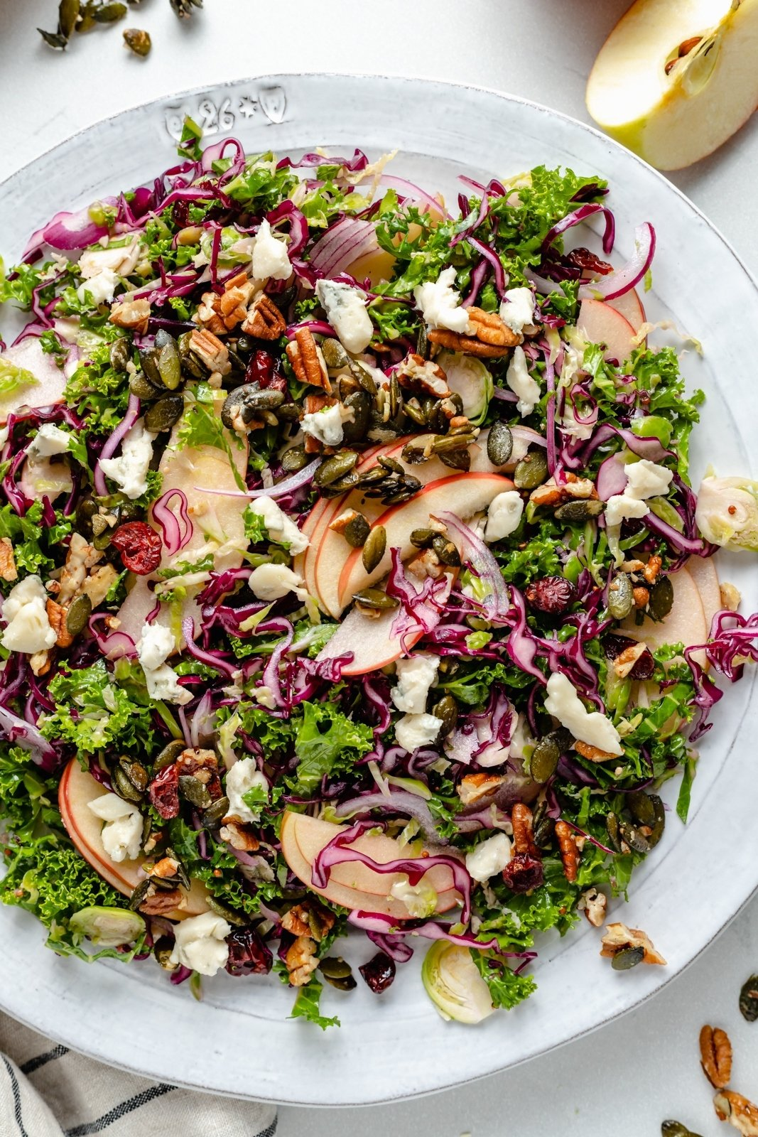 kale apple salad with nuts and gorgonzola on a plate
