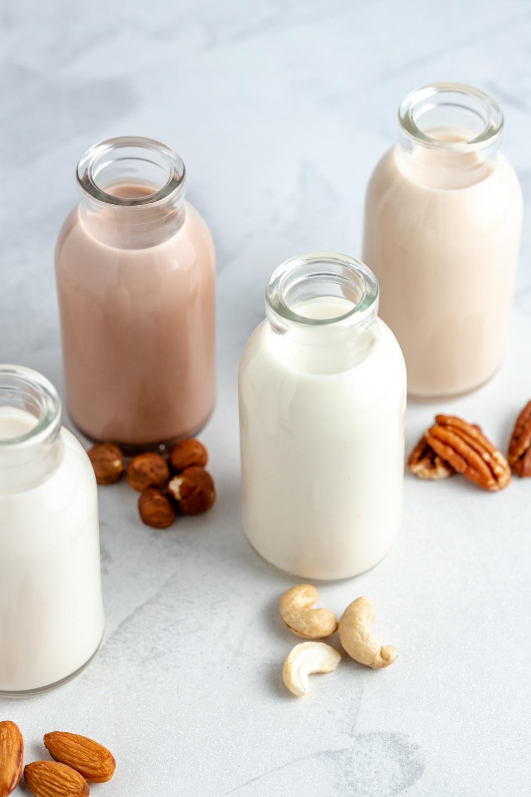 homemade nut milks in four separate jars