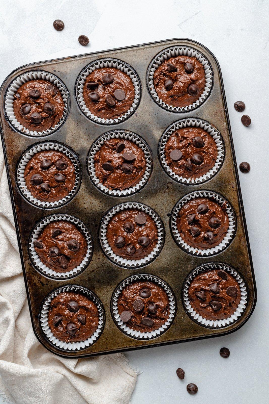 unbaked almond butter chocolate pumpkin muffins in a muffin tin