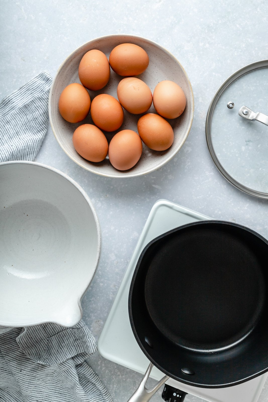 eggs, a bowl and a pot next to each other