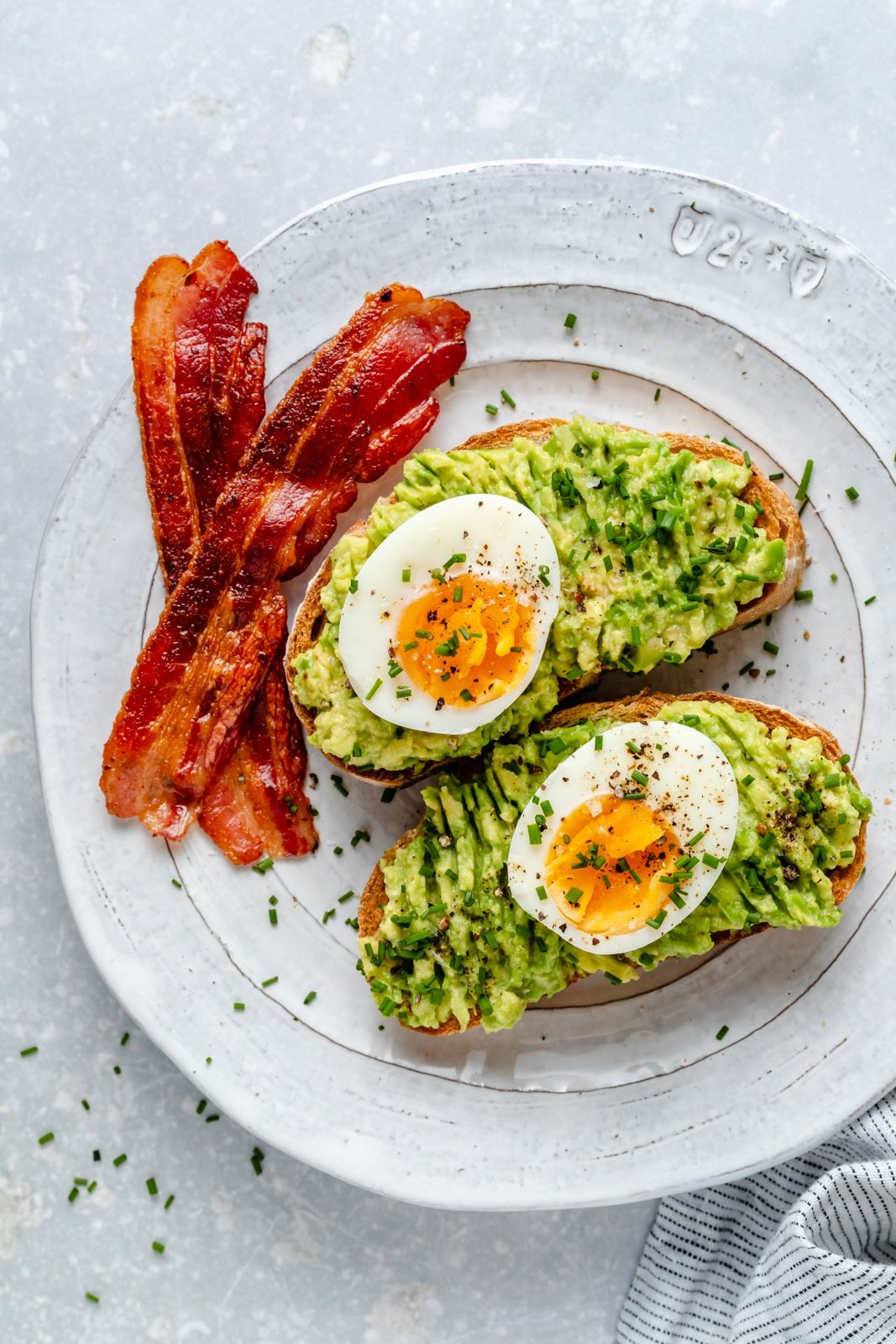 hard boiled eggs on avocado toast with a side of bacon