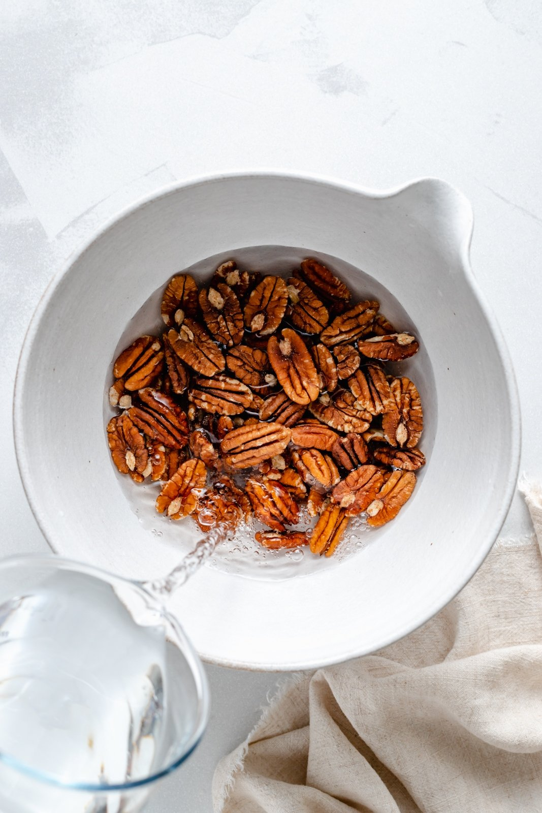 pouring water into a bowl of pecans