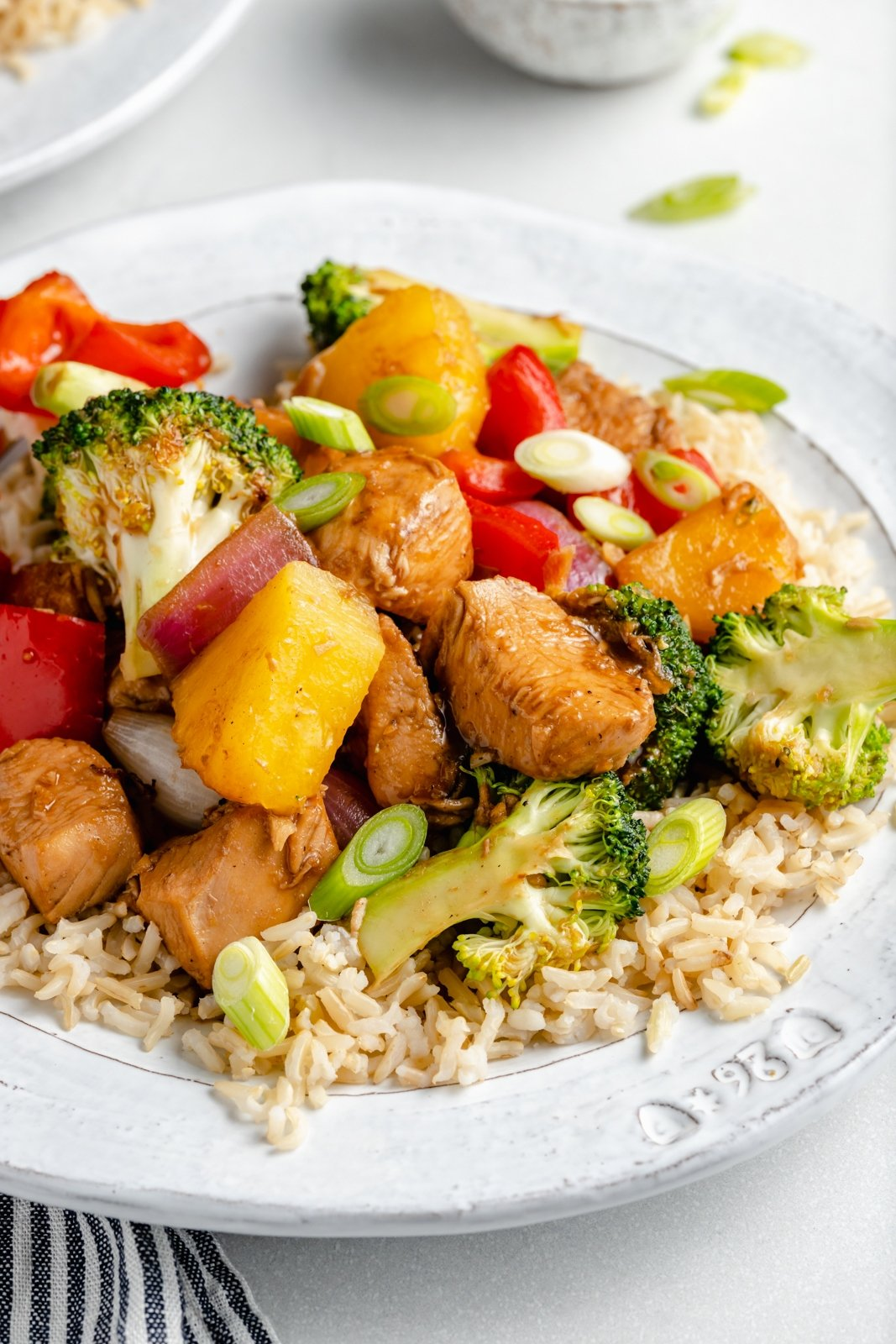 pineapple chicken stir fry with broccoli on a plate