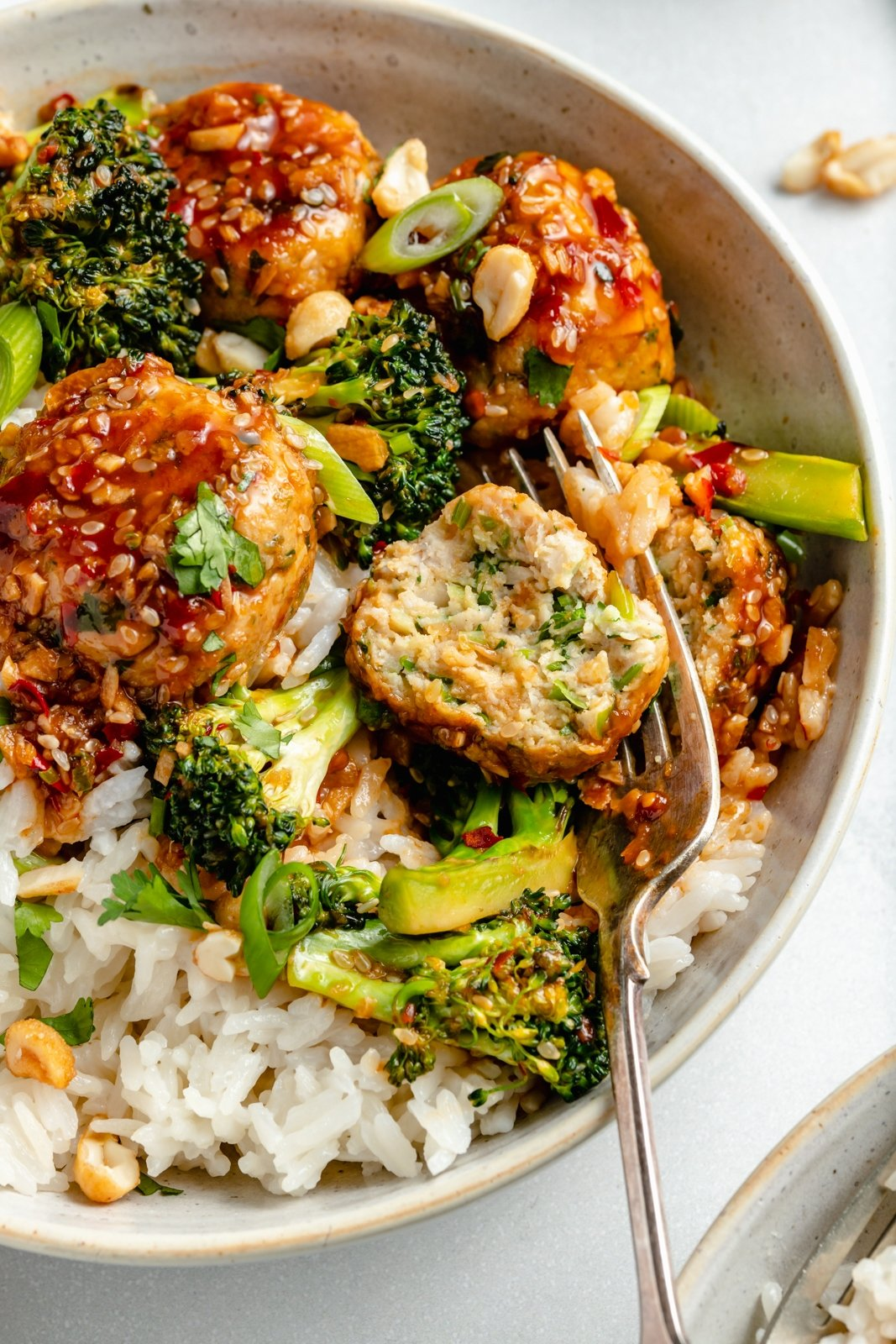 up-close view of healthy sesame chicken meatballs bowls with rice and broccoli