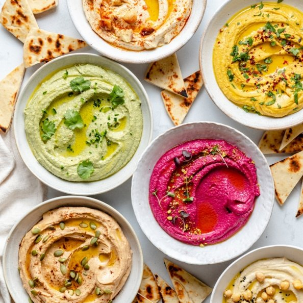 five bowls of homemade hummus on a board