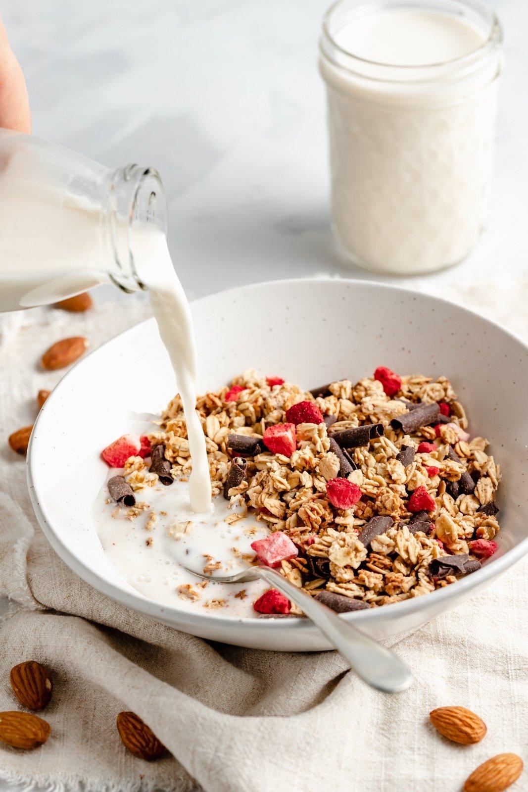 pouring homemade vanilla almond milk into a bowl of granola