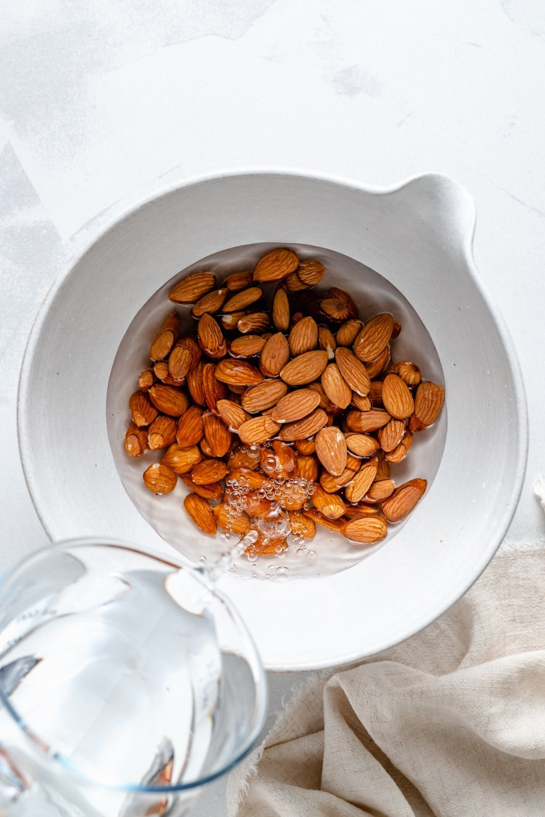 pouring water into a bowl of almonds