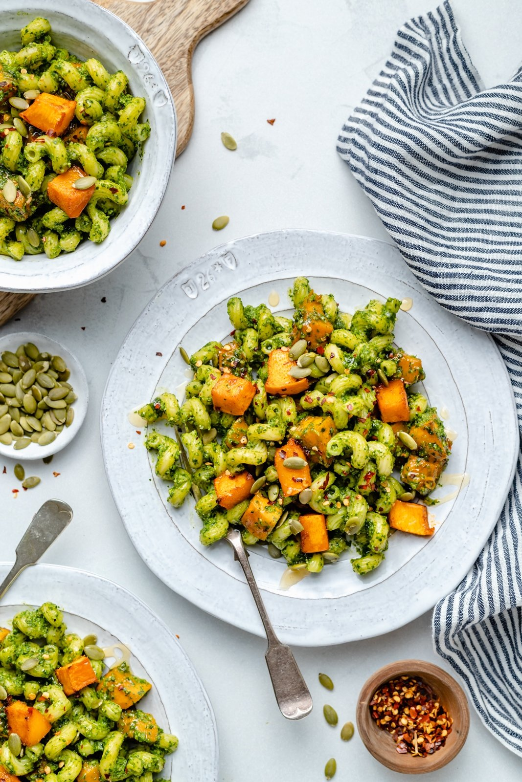 vegetarian cilantro pesto pasta on plates with roasted pumpkin