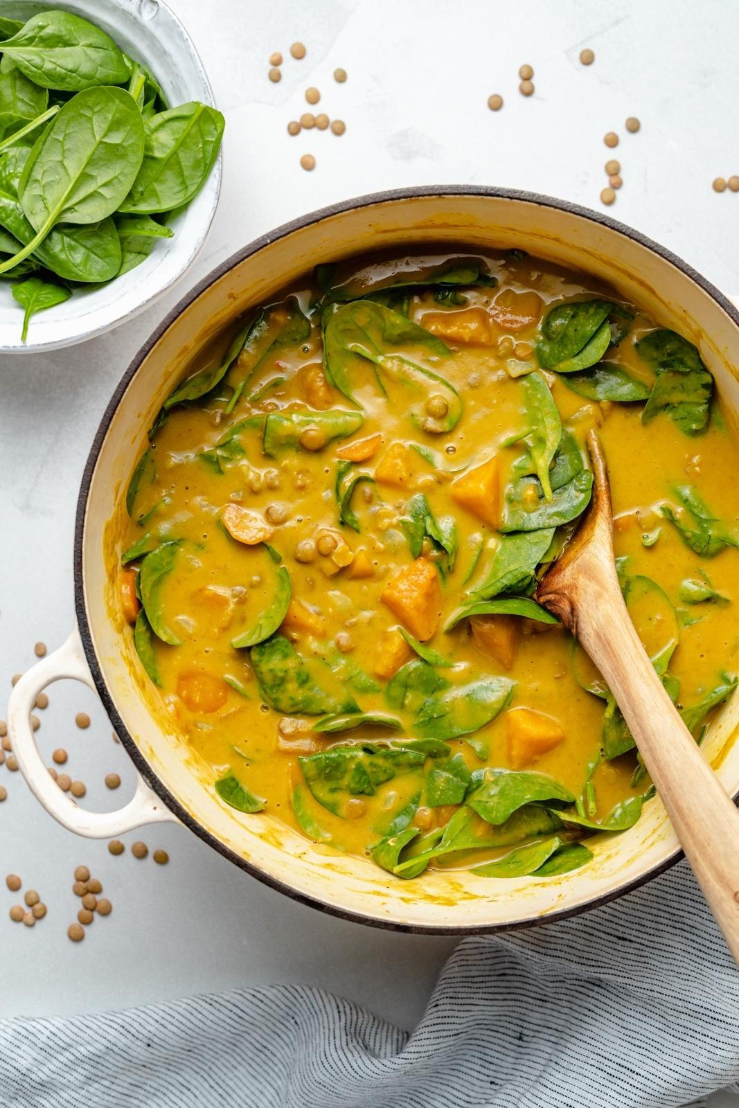 vegane Butternut-Kürbis-Linsensuppe im Topf mit Spinat