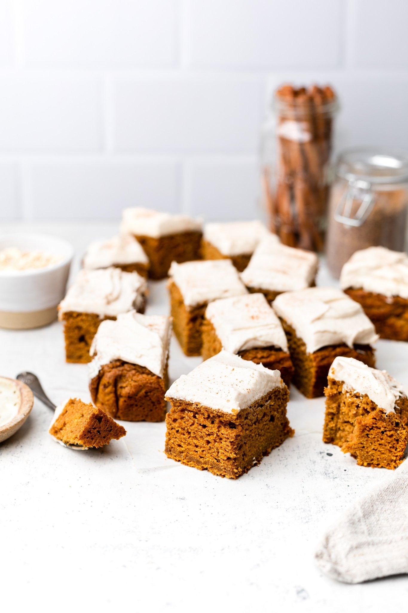 healthy pumpkin cake with frosting cut into squares